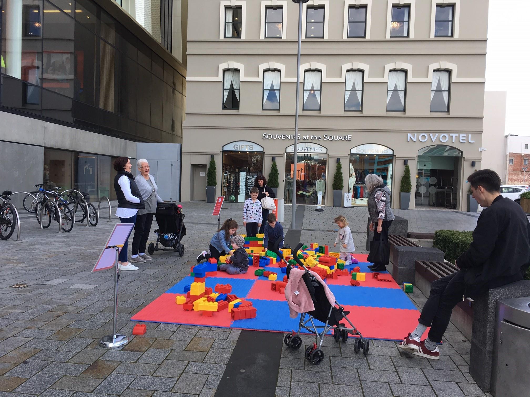 Children play on giant lego blocks on ground mats.