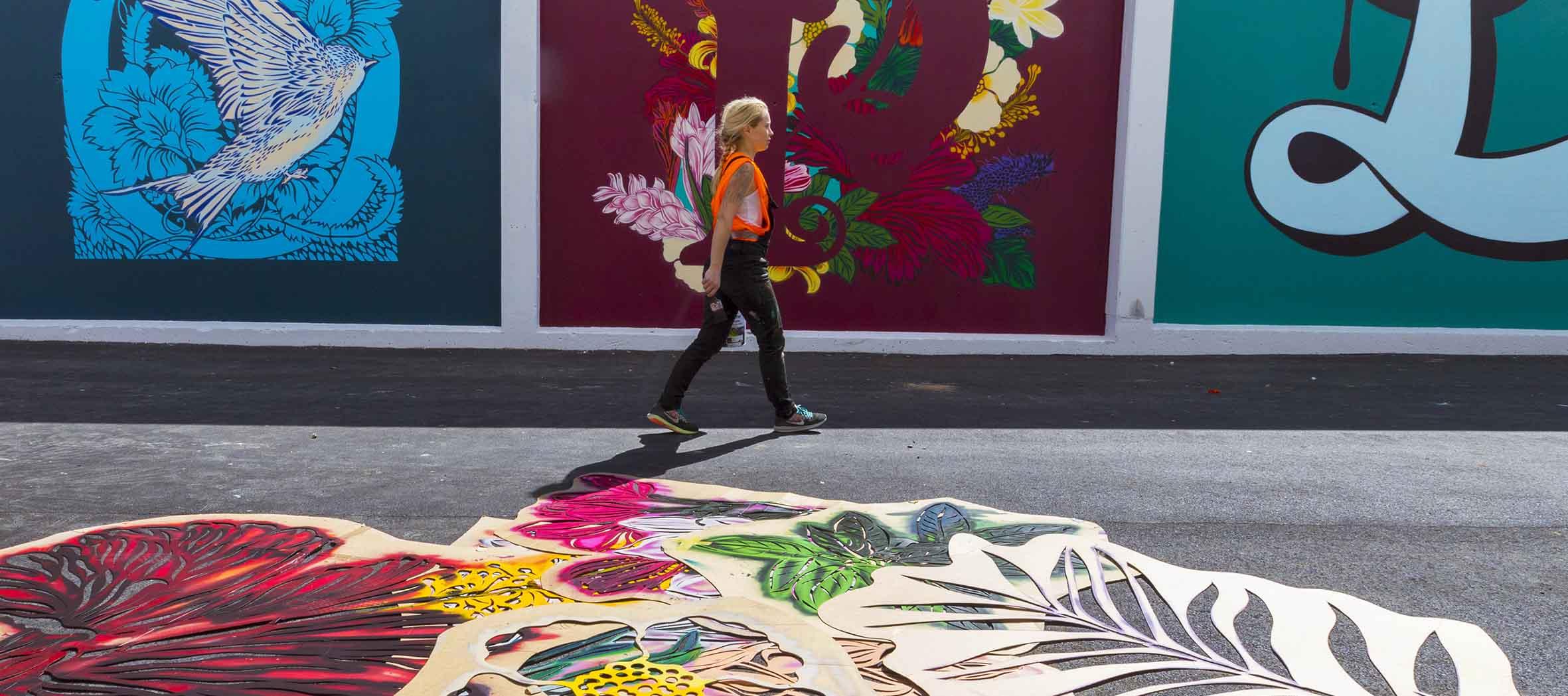 An artist walks in front of her work in progress.
