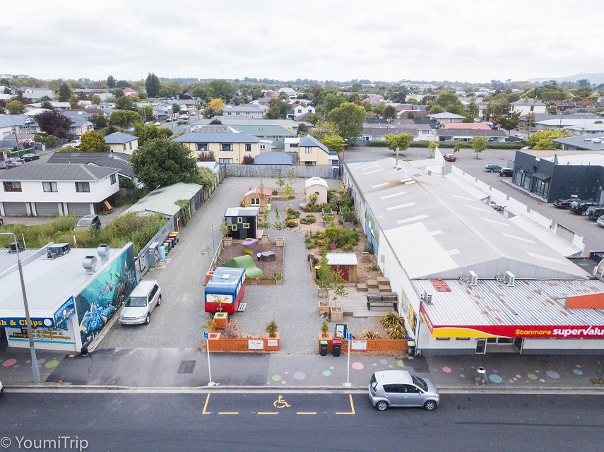 An aerial view of a site hosting small colourful huts