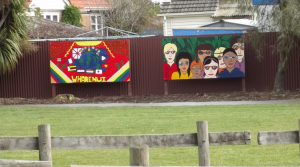 Two murals on sign boards in a grassed area