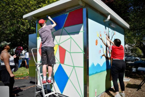 People painting a toilet block with bright colours