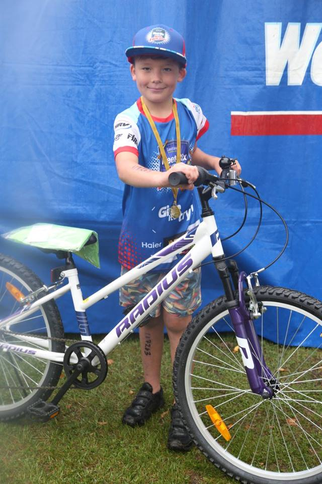 Young male participant in a previous Sanitarium Weet-Bix Kids TRYathlon with his bike.